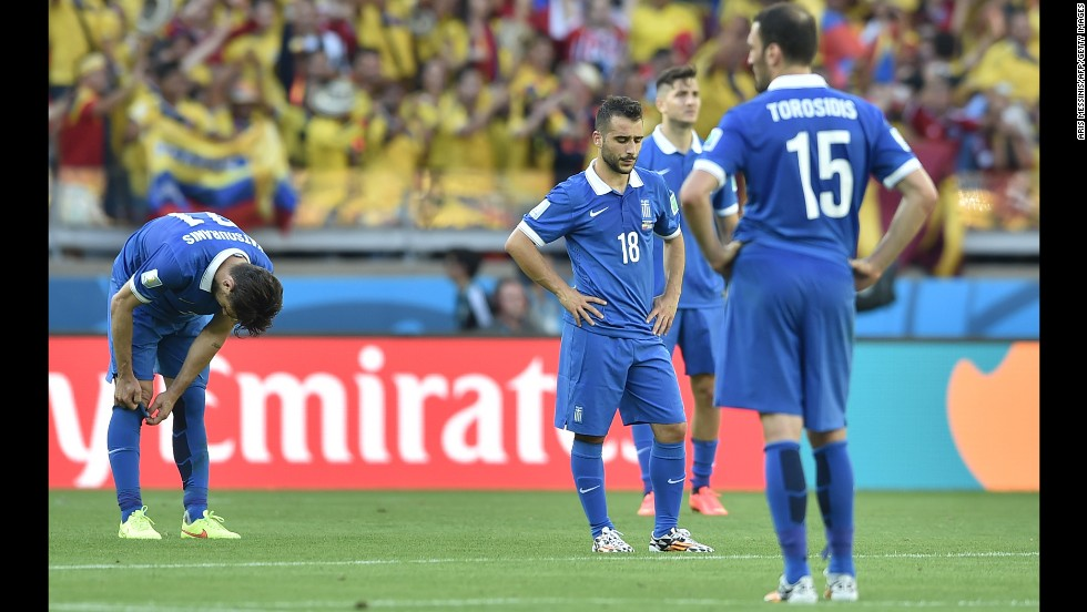 Greece forward Ioannis Fetfatzidis, second left, and defender Vasilis Torosidis, right, react after conceding the third goal in time added on.