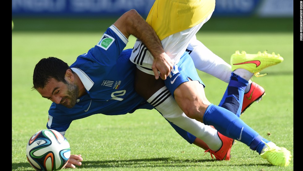 Greece midfielder Giorgos Karagounis tumbles to the ground as he tussles with Colombia forward Jackson Martinez.