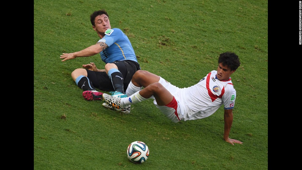 Uruguay midfielder Cristian Rodriguez, left,  falls to the ground with Costa Rica counterpart Yeltsin Tejeda.