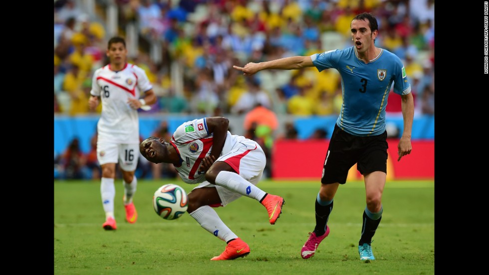 Uruguay defender Diego Godin, right, gestures as Costa Rica forward Joel Campbell, center, falls.