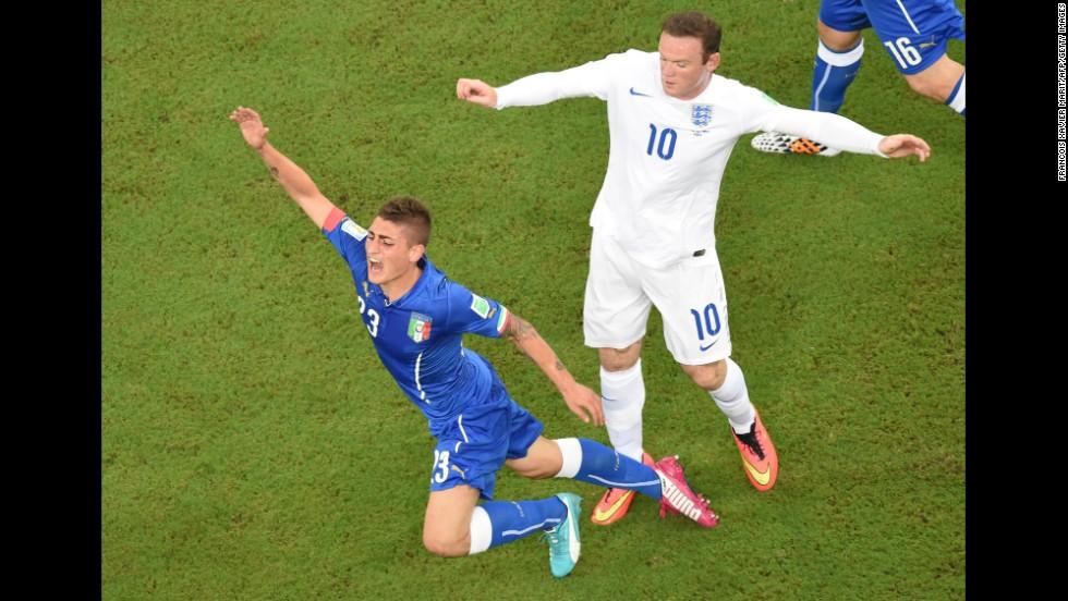 Italy midfielder Marco Verratti, left, falls following a tackle by England forward Wayne Rooney.