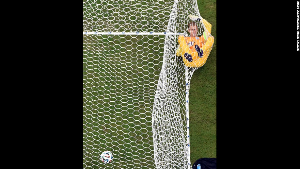 England's goalkeeper Joe Hart lies in the net after Mario Balotelli put Italy 2-1 up in the World Cup match at the Amazonia Arena in Manaus, Brazil.