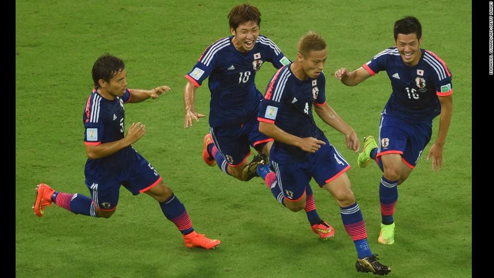 Keisuke Honda of Japan, second from right, celebrates scoring his team's first goal with Yuto Nagatomo, left, Yuya Osako, second from left, and Hotaru Yamaguchi, right