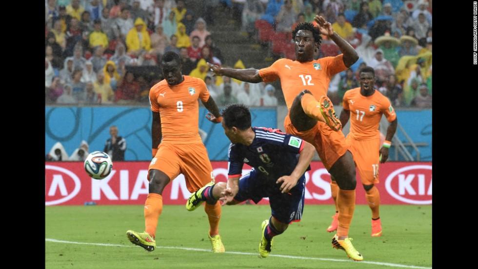 Japan forward Shinji Okazaki, center, heads the ball past Ivory Coast forward Wilfried Bony.