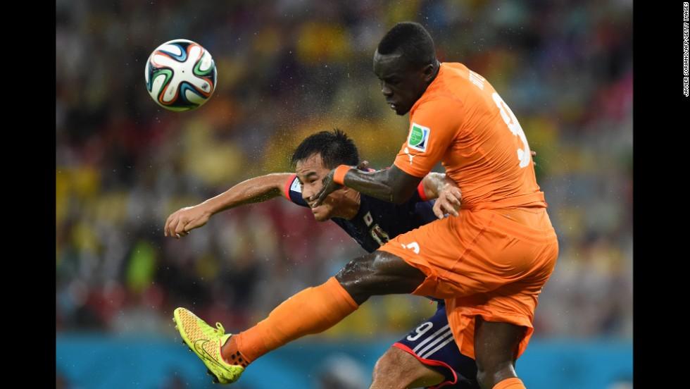 Japan forward Shinji Okazaki, left, heads the ball past Ivory Coast midfielder Cheick Tiote.