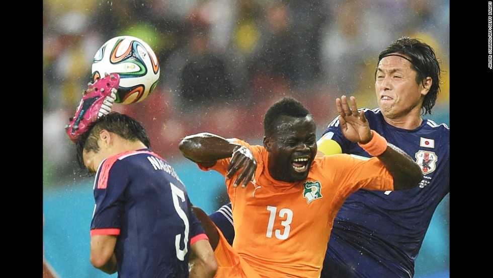 Ivory Coast midfielder Didier Ya Konan vies with a couple of Japan players for control of  the ball.