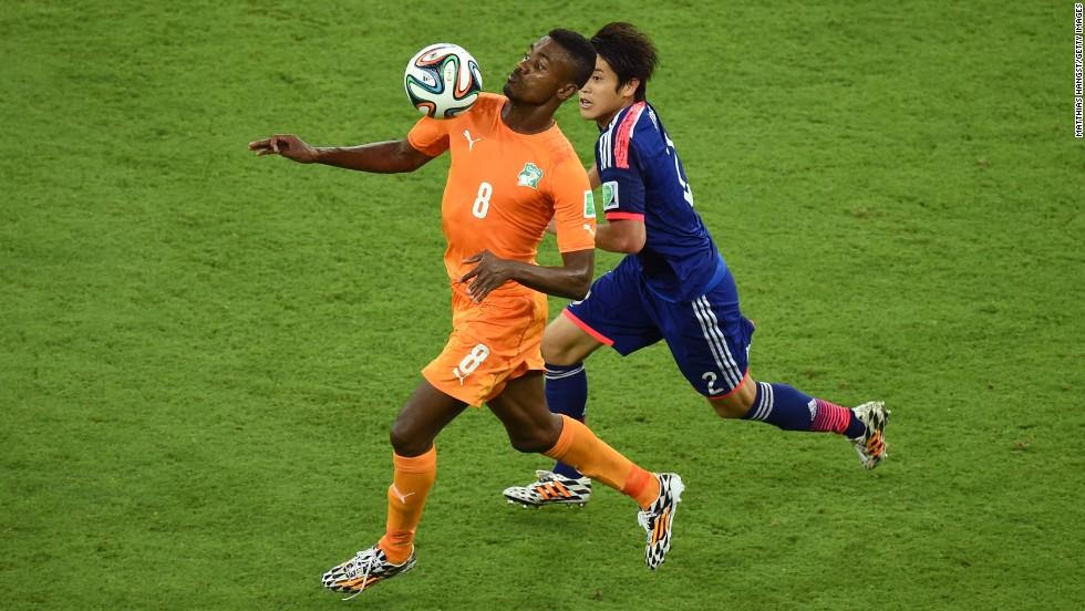 Salomon Kalou of the Ivory Coast controls the ball against Atsuto Uchida of Japan.