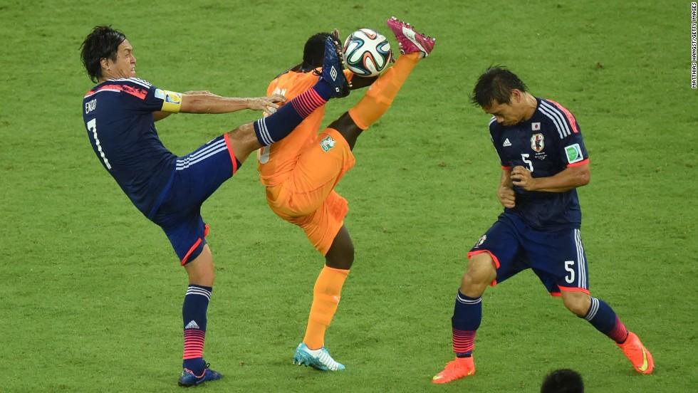 Didier Ya Konan of the Ivory Coast competes for the ball with Yasuhito Endo, left, and Yuto Nagatomo of Japan.