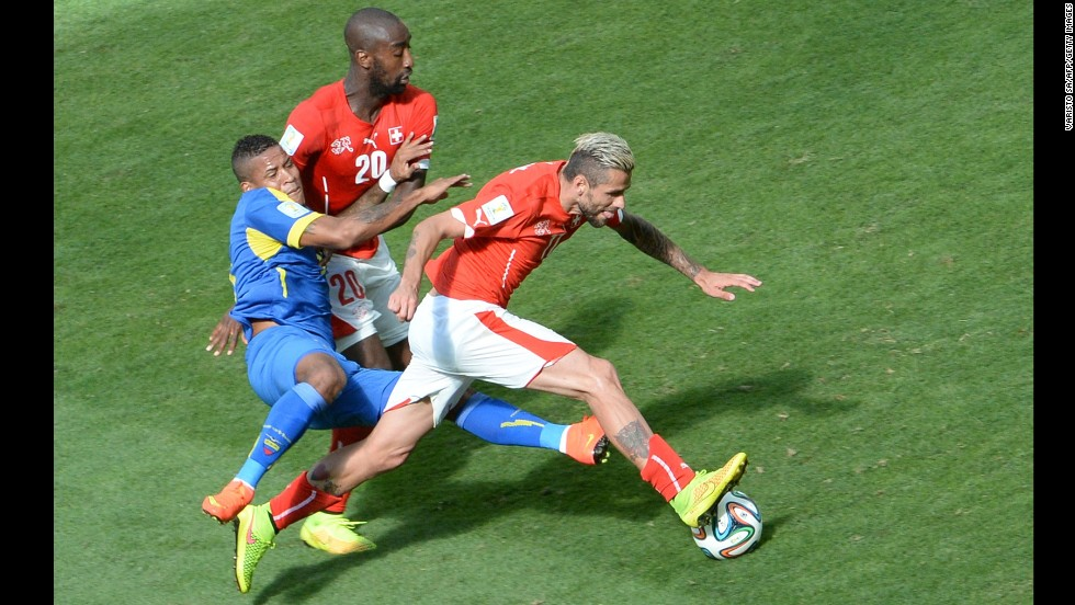 Switzerland midfielder Valon Behrami, right, is tackled by Ecuador's Michael Arroyo, left.