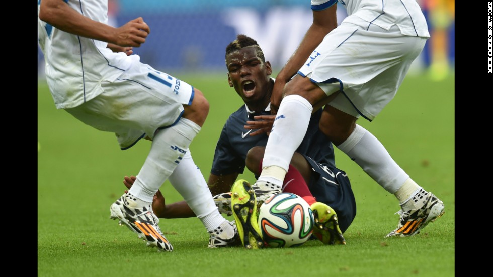 France midfielder Paul Pogba is tackled by Honduras' Wilson Palacios, right.