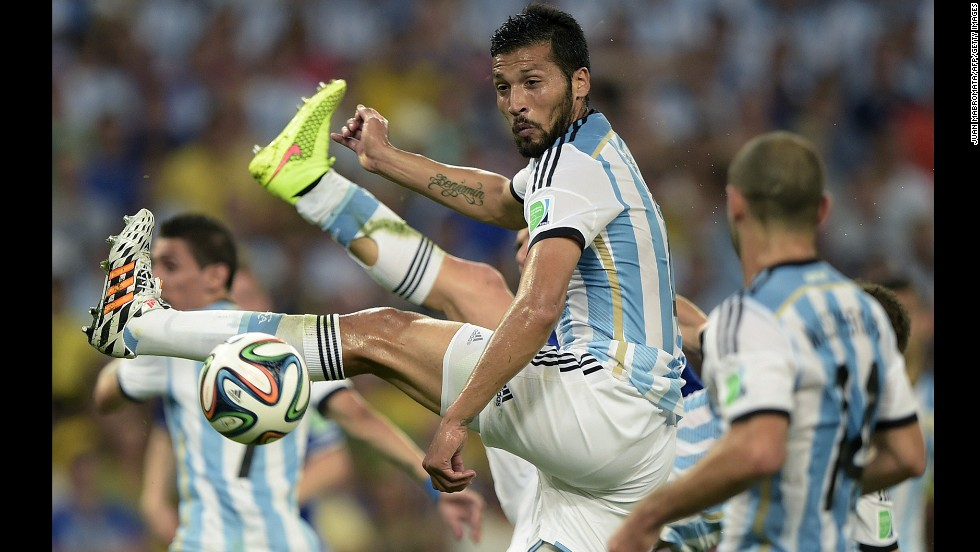 Argentina defender Ezequiel Garay jumps to kick the ball.