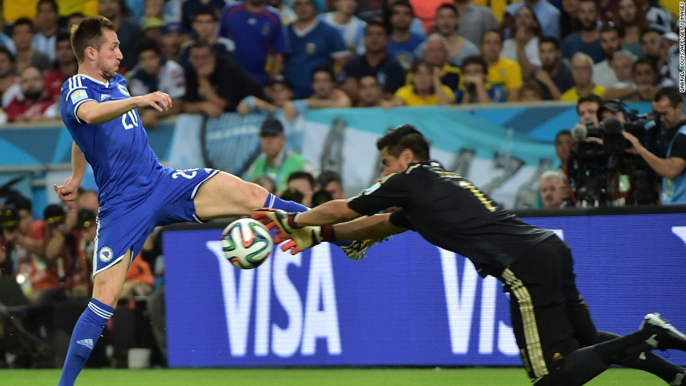 Bosnia-Herzegovina midfielder Izet Hajrovic fights for the ball with Argentina's goalkeeper Sergio Romero.
