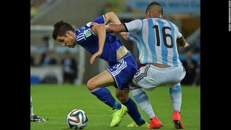 Argentina defender Marcos Rojo, right,  challenges Bosnia-Herzegovina defender Ermin Bicakci.