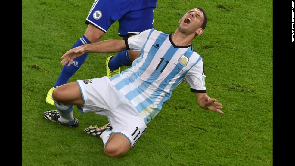 Argentina midfielder Maxi Rodriguez reacts after a tackle by Bosnia-Herzegovina defender Muhamed Besic.