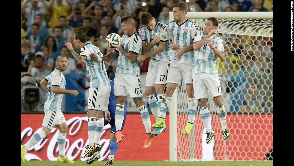 Argentina players leap to block a free-kick by the opposing team.
