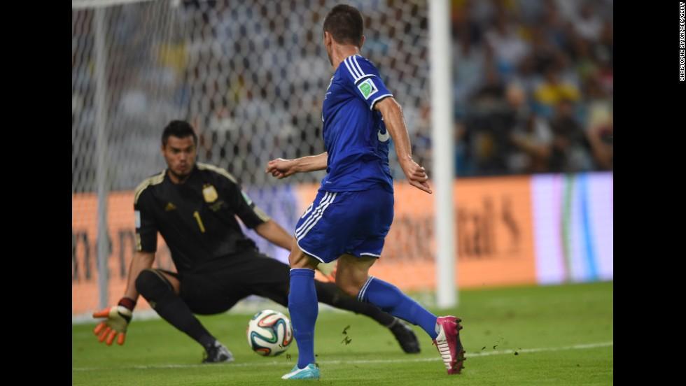Substitute Vedad Ibisevic shoots past Argentina goalkeeper Sergio Romero to score Bosnia-Herzegovina's historic first World Cup goal Sunday, June 15, at the Maracana Stadium in Rio de Janeiro. But Argentina won the match 2-1.