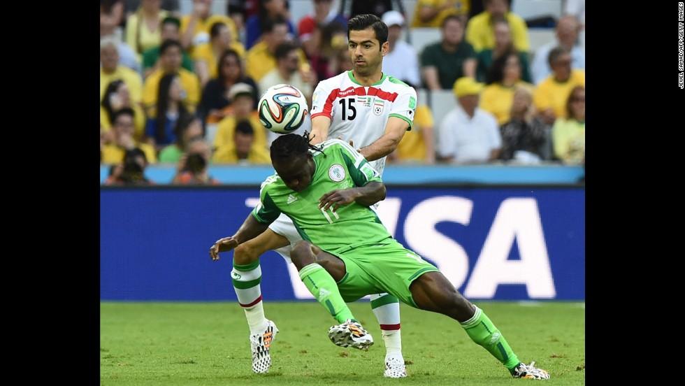 Iranian defender Pejman Montazeri (No. 15) challenges Nigeria's Victor Moses.