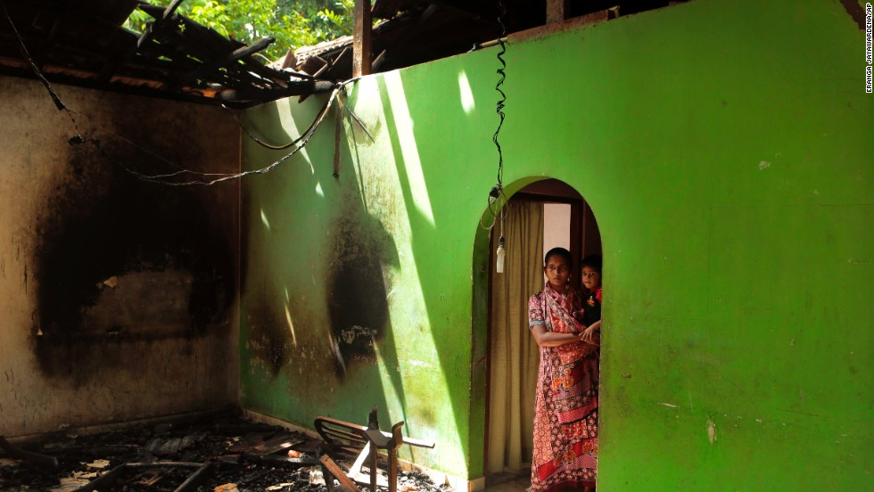 A Muslim mother and child take in damage to their house.
