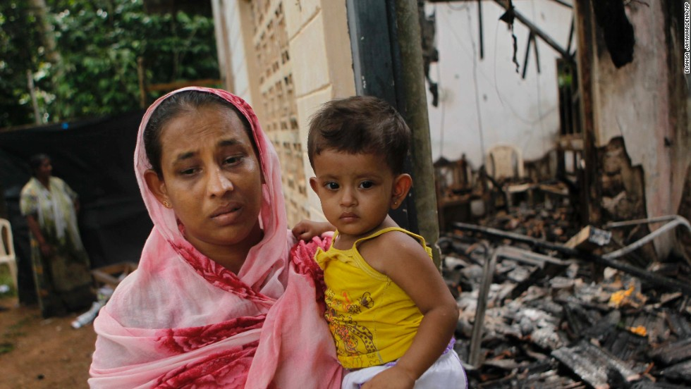 A Sri Lankan Muslim woman carries her daughter outside her burnt house after at least  three Muslims were killed and 80 injured in clashes with Buddhists last month. The sectarian riots in and around the town of Aluthgama, in southern Sri Lanka, followed demonstrations by the hardline Buddhist group Bodu Bala Sena, police said. Homes and shops were looted and burned.