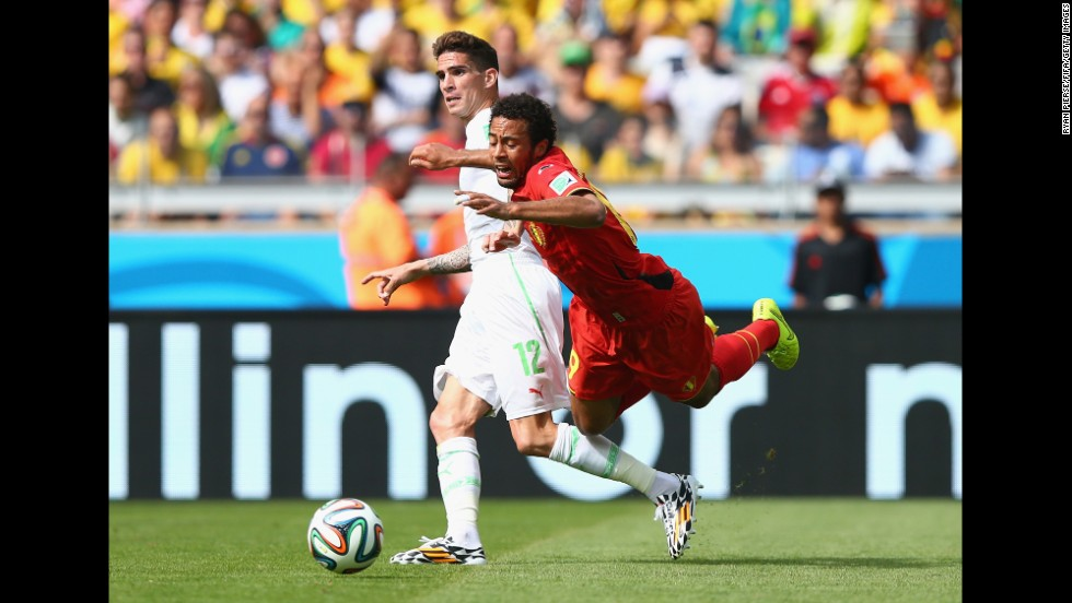 Moussa Dembele of Belgium goes down next to Carl Medjani of Algeria.