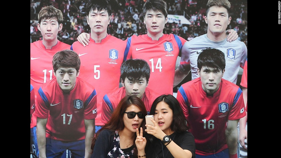 Women take a selfie in front of a picture of the South Korean national soccer team Monday, June 16, in Seoul, South Korea.