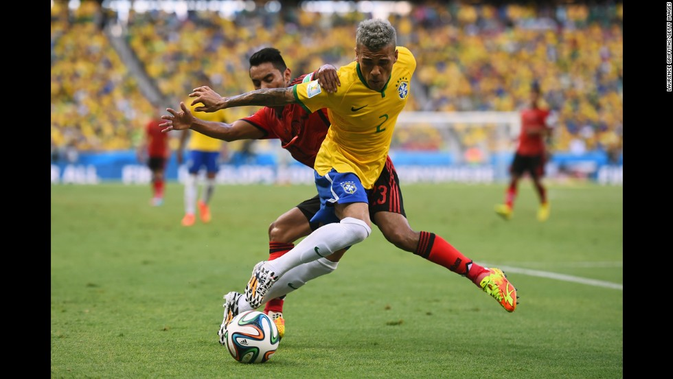 Dani Alves of Brazil, front, and Vazquez battle for the ball.