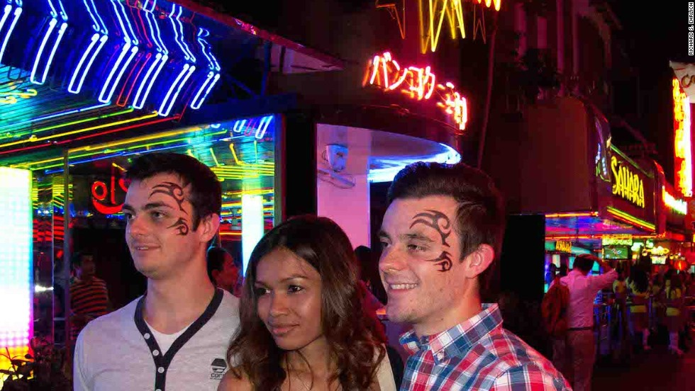 "British tourists Cameron Johnson and his brother, Brad, accompanied by a Hangover Tour guide, on Soi Cowboy. The tattoo sticker ""acts like a mask ... and you just forget about who you are back home, and you just sort of go with it,"" says Brad."