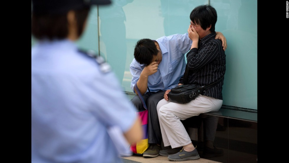 A police officer watches a crying couple cry outside the airline's office building in Beijing after officials refused to meet with them on June 11, 2014. The couple's son was on the plane.