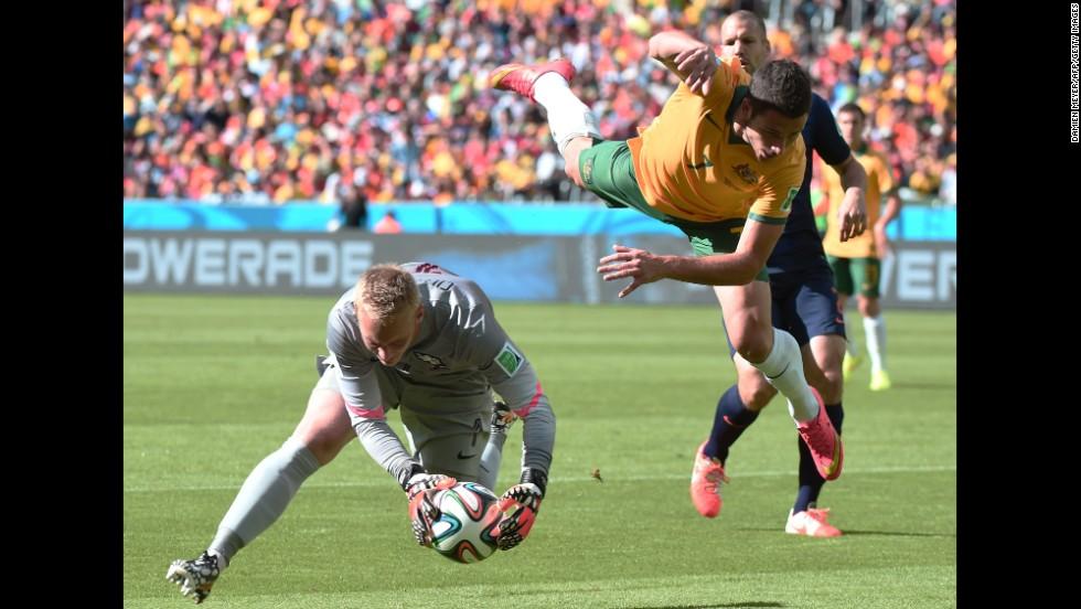 Netherlands goalkeeper Jasper Cillessen corrals the ball while Australia's Mathew Leckie leaps through the air.