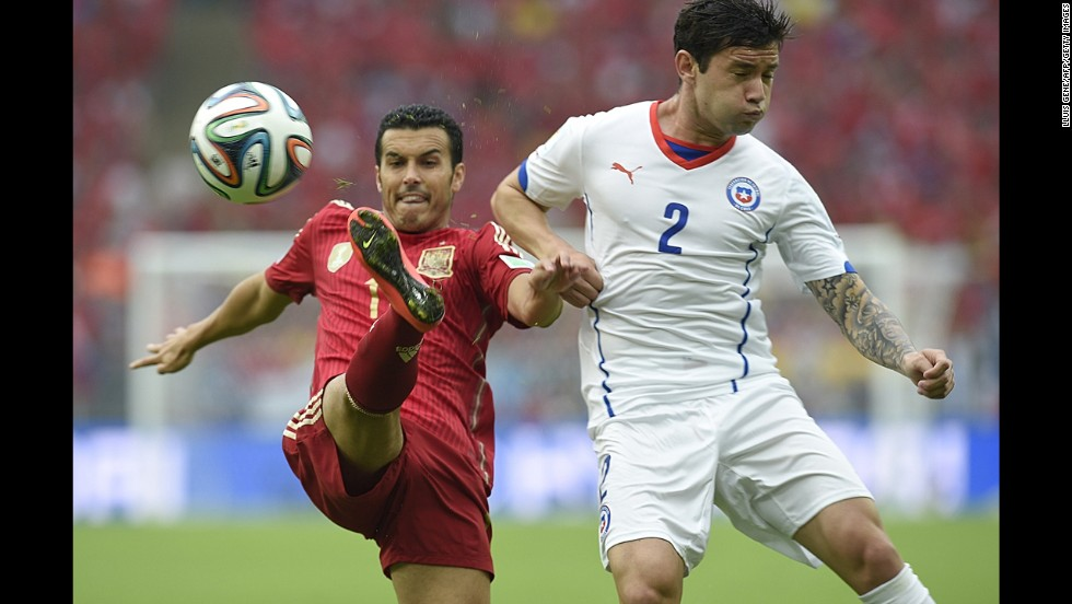 Pedro, left, kicks the ball near Chilean defender Eugenio Mena.