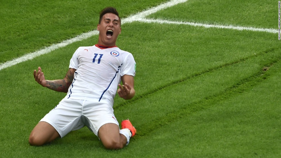 Chile forward Eduardo Vargas slides on the grass after scoring the game's opening goal.