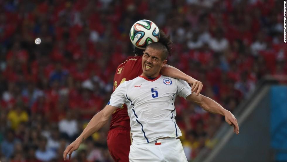 Spain midfielder David Silva, left, and Chile midfielder Francisco Silva compete for the ball.