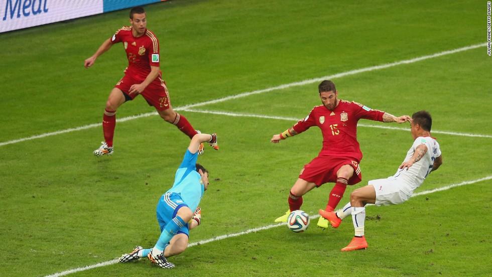 Eduardo Vargas, right, scores Chile's first goal, firing past Spanish goalkeeper Iker Casillas.