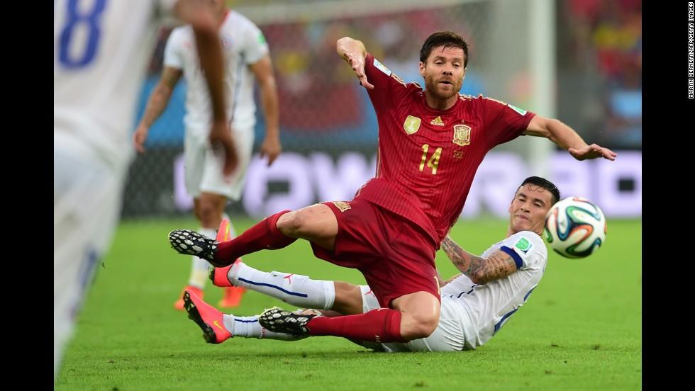 Spanish midfielder Xabi Alonso, left, falls to the ground near Chilean midfielder Charles Aranguiz.