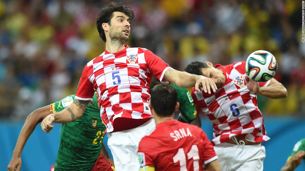 Croatian defender Vedran Corluka, center, heads the ball.