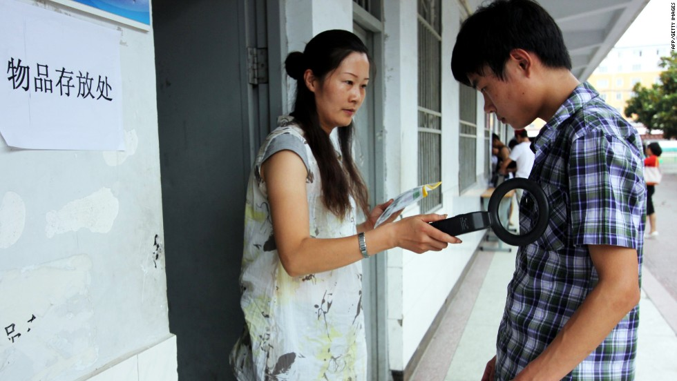 An invigilator checks a student before the 2013 entrance exam starts in Zhoukou, in central China's Henan province, on June 7, 2013.