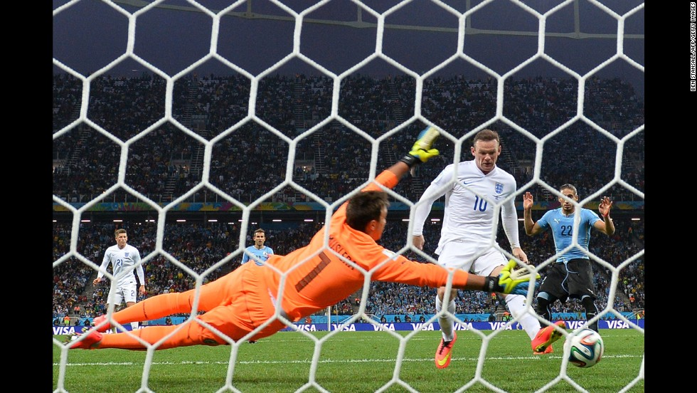 England forward Wayne Rooney taps the ball past Uruguay goalkeeper Fernando Muslera to tie the match at 1-1. It was Rooney's first World Cup goal in his career.