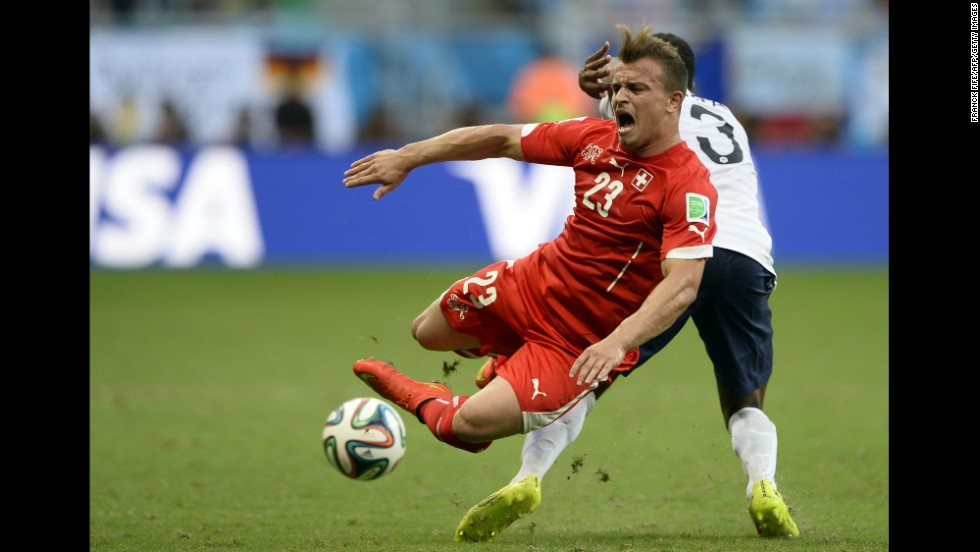 Switzerland midfielder Xherdan Shaqiri falls over during a challenge by France defender Patrice Evra.