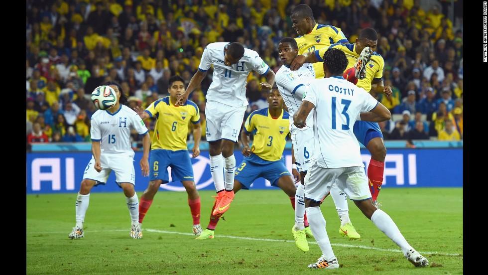 Enner Valencia of Ecuador scores his team's second goal on a header against Jerry Bengtson and Juan Carlos Garcia of Honduras on Friday, June 20, in Curitiba, Brazil. The goal brought the score to 2-1, Ecuador.