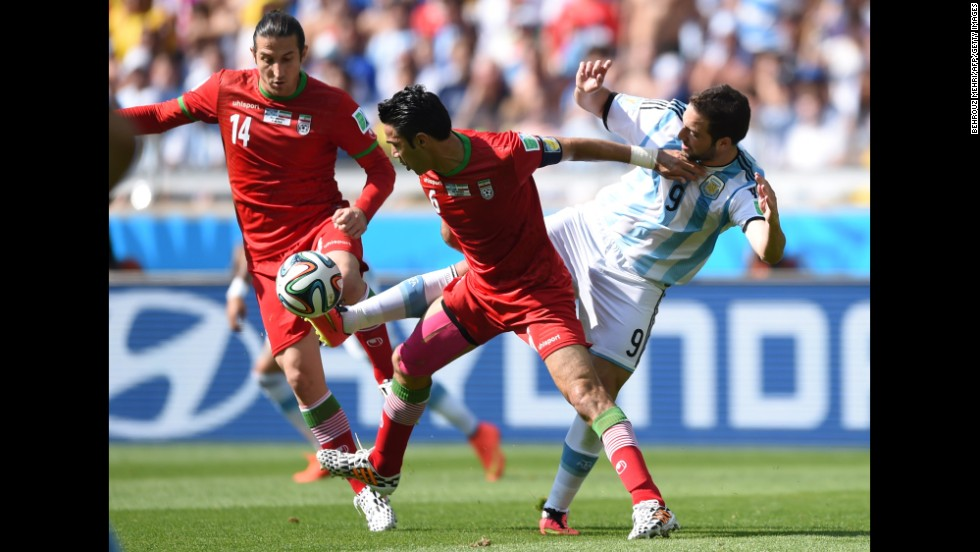 Iran midfielders Andranik Teymourian and Javad Nekounam battle for the ball against Argentina forward Gonzalo Higuain.