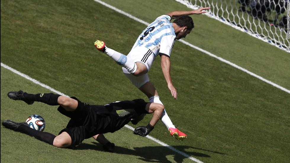 Argentina forward Gonzalo Higuain, right, and Iran's goalkeeper Alireza Haqiqi vie  for the ball.