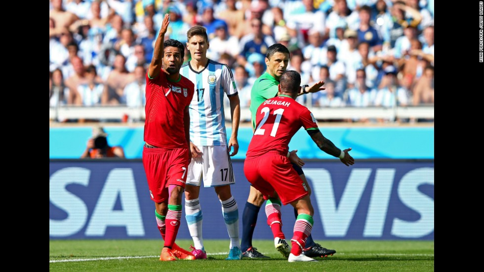 Members of the Iranian team appeal to referee Milorad Mazic, claiming Argentina's Pablo Zabaleta fouled Ashkan Dejagah of Iran.