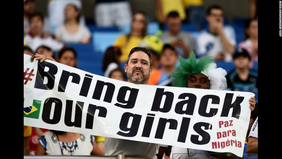 "A man holds a banner reading ""Bring back our girls"" ahead of the match between Nigeria and Bosnia-Herzegovina. The sign is a reference to the abduction of more than 200 Nigerian schoolgirls in April."