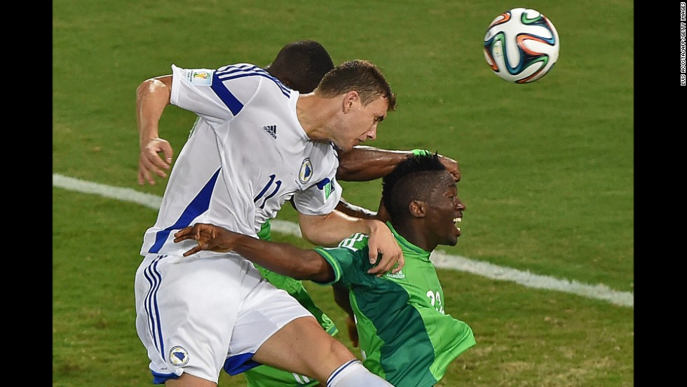 Bosnia- Herzegovina forward Edin Dzeko, left, heads the ball near Nigeria defender Kenneth Omeruo.