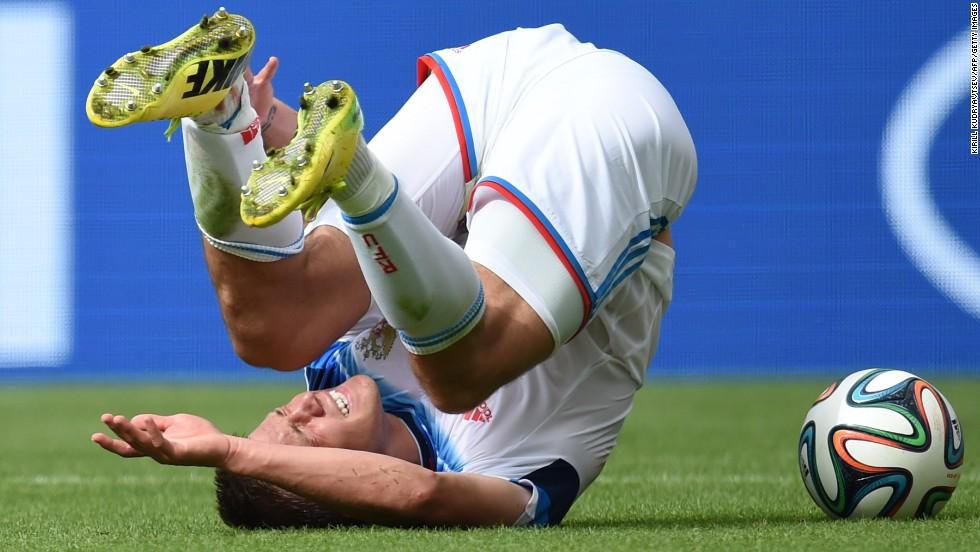 Russia's forward Maxim Kanunnikov tumbles.