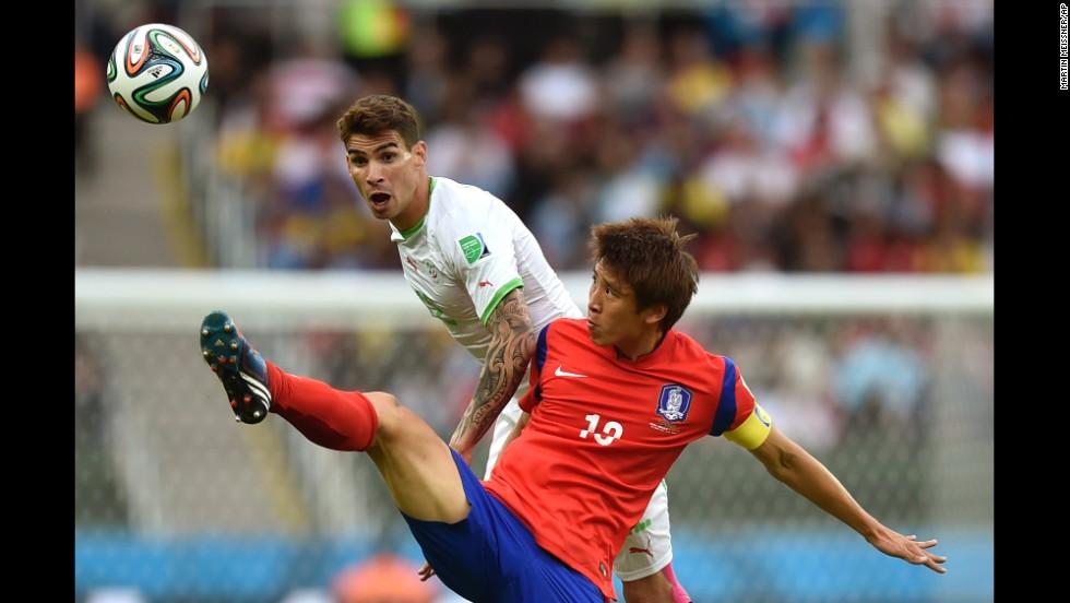 South Korea's Koo Ja-cheol reaches for the ball in front of Algeria's Carl Medjani.