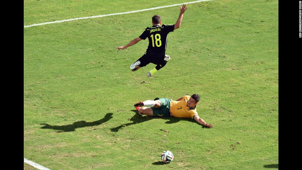 Spain defender Jordi Alba, top, vies with Australia forward Mathew Leckie.