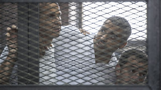 Journalists Peter Greste, left, Mohamed Fadel Fahmy, center, and Baher Mohamed on June 23, 2014 during their Cairo trial.