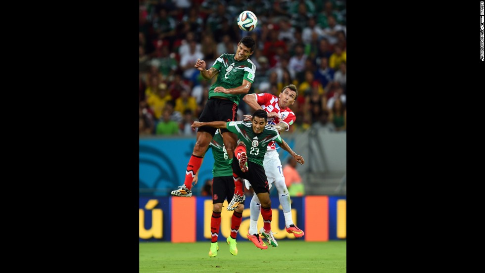 Francisco Javier Rodriguez (in green) of Mexico goes up for a header against Mario Mandzukic (in red and white) of Croatia.