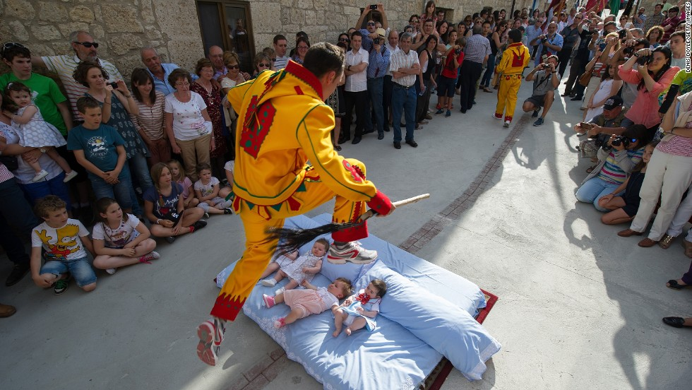 CASTRILLO DE MURCIA, SPAIN - JUNE 22: A man representing the devil leaps over babies during the festival of El Salto del Colacho (The Devil's Jump). The tradition, which dates back to the 17th century, is believed to cleanse babies of original sin and protect them from illness.